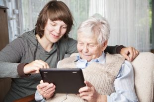 young woman and senior woman using digital tablet