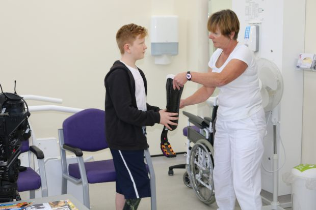 Ben, 13, receives his running blade from prosthetist Clare Johnson